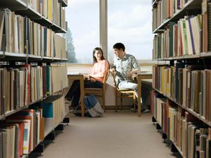 Teenagers doing homework in libraryの写真素材 [FYI03632366]