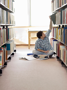 Student sitting on floor in library  reaching for bookの写真素材 [FYI03632368]