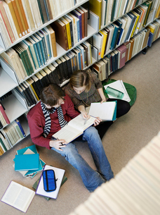 Students sitting on floor  doing homework in libraryの写真素材 [FYI03632375]