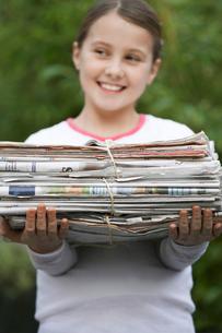 Girl (10-12) holding bundle of waste paper  smiling  lookiの写真素材 [FYI03632392]