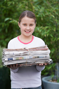 Girl (10-12) holding bundle of waste paper  smilingの写真素材 [FYI03632393]