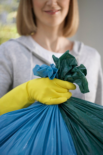 Woman wearing rubber gloves  holding garbage bag  close-upの写真素材 [FYI03632400]