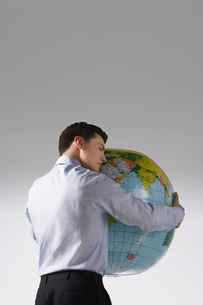 Young adult man with arms around big globe  back viewの写真素材 [FYI03632425]