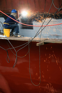 Welder working on side of ship in dry dockの写真素材 [FYI03632445]