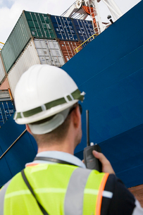 Man wearing hard hat using walkie-talkie at container termの写真素材 [FYI03632452]