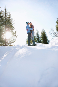 Couple standing on snow-covered hill  low angle viewの写真素材 [FYI03632469]