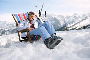 Female skier sitting on deckchair in mountainsの写真素材 [FYI03632480]