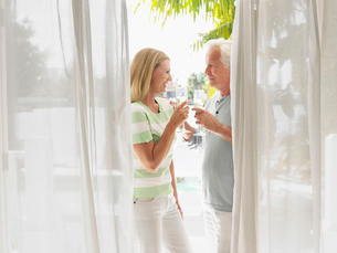 Couple toasting with champagne flutes  standing on verandaの写真素材 [FYI03632512]