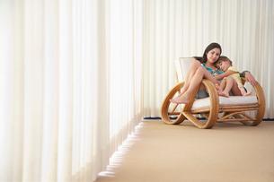 Teenage girl (16-18) sitting on armchair with sister (5-6)の写真素材 [FYI03632566]