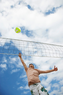 Teenage boy (16-17) playing volleyball  low angle viewの写真素材 [FYI03632570]