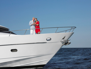 Middle-aged couple standing in bow of yachtの写真素材 [FYI03632594]
