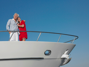 Middle-aged couple standing in bow of yachtの写真素材 [FYI03632598]
