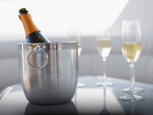 Flutes and champagne in ice bucket on tableの写真素材 [FYI03632602]