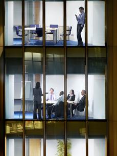 Business man text messaging on floor above group of busineの写真素材 [FYI03632651]