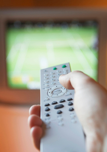 Man adjusting TV channel volume with remote control  closeの写真素材 [FYI03632660]