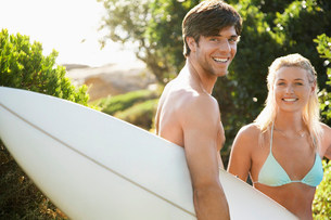 Young couple in swimwear  man holding surfboard  outsideの写真素材 [FYI03632690]