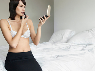 Young woman in underwear sitting on bed  applying make-upの写真素材 [FYI03632715]