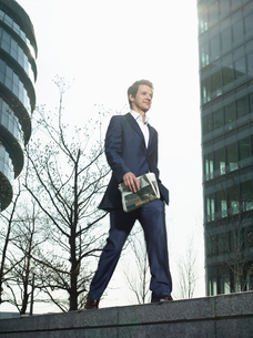 Young man in suit walking on wall outside office buildingの写真素材 [FYI03632730]