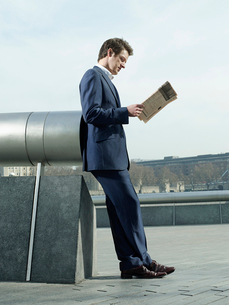 Young man in suit leaning on pipe outdoors  reading paperの写真素材 [FYI03632736]