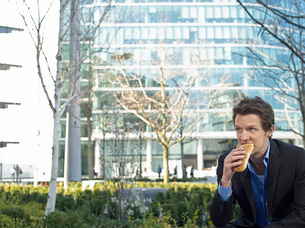 Mid adult businessman sitting in front of office buildingの写真素材 [FYI03632753]