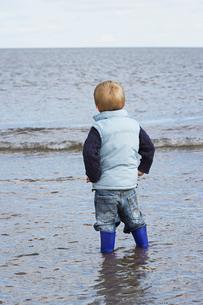 Boy (3-4) wearing wellington boots  standing in oceanの写真素材 [FYI03633026]