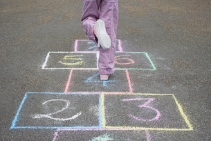 Girl (7-9) playing hop-scotch in school playground  low seの写真素材 [FYI03633047]