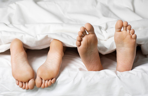 Couple lying in bed  low section  close up of feetの写真素材 [FYI03633110]