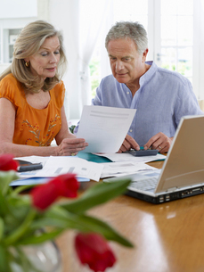Senior couple looking at bills  sitting at dining tableの写真素材 [FYI03633112]