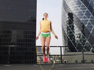 Woman skipping on skipping rope on downtown rooftop  low aの写真素材 [FYI03633141]