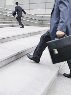 Business men hurrying up steps  outdoors  side viewの写真素材 [FYI03633176]