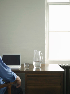 Person sitting at desk with laptop and jug of water  backの写真素材 [FYI03633234]