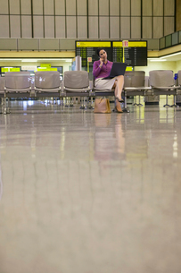 Business woman using laptop and mobile phone in airport loの写真素材 [FYI03633266]