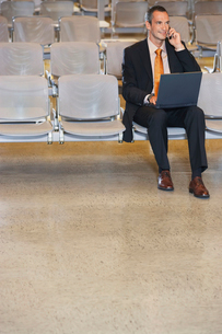 Business man using mobile phone and laptop in airport lobbの写真素材 [FYI03633289]