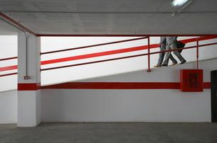 Two businessmen walking down ramp in parking garageの写真素材 [FYI03633303]