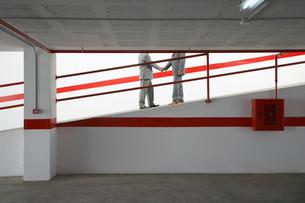 Two businessmen shaking hands on ramp in parking garageの写真素材 [FYI03633305]