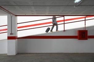 Businessman walking up ramp in parking garage with luggageの写真素材 [FYI03633306]