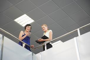 Two women looking over railing of indoor balconyの写真素材 [FYI03633325]