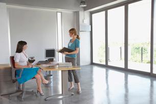 Two women talking at desk in empty office buildingの写真素材 [FYI03633335]