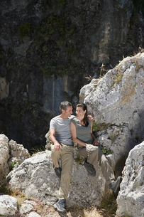 Couple sitting on mountain top  elevated viewの写真素材 [FYI03633350]