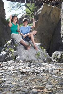 Boy and girl (10-12) sitting on rock  throwing stonesの写真素材 [FYI03633357]