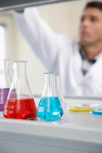 Scientist working in laboratory  focus on beakers in foregの写真素材 [FYI03633417]