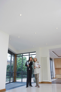 Real estate agent and woman observing new propertyの写真素材 [FYI03633453]