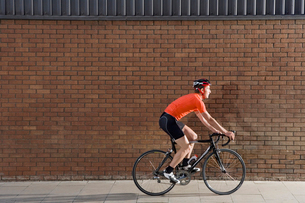 Man cycling past brick wallの写真素材 [FYI03633455]
