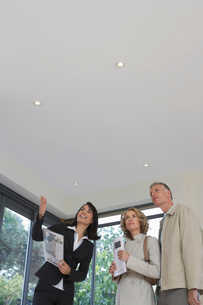 Real estate agent and couple observing new propertyの写真素材 [FYI03633457]