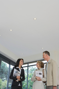 Real estate agent and couple observing new propertyの写真素材 [FYI03633459]