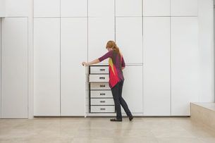 Woman looking in wardrobe in empty apartmentの写真素材 [FYI03633472]