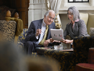 Business man and woman sitting indoors looking at documentの写真素材 [FYI03633488]
