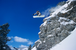 Person on snowboard  jumping  low angle viewの写真素材 [FYI03633513]