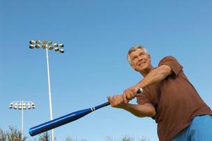 Senior man swinging baseball batの写真素材 [FYI03633576]