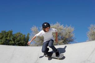 Teenage boy skateboarding at skate parkの写真素材 [FYI03633577]